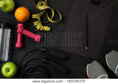 Athlete's set with female clothing, sneakers and bottle of water on dark background. Top view. Copy space. Still life. Ideal for sporty blog.