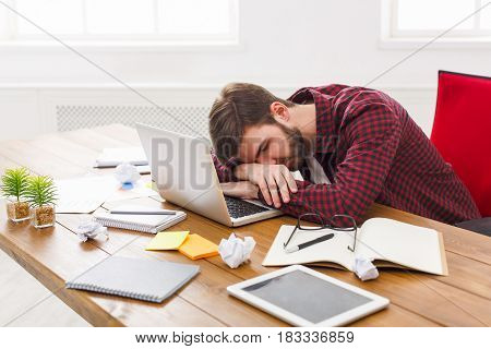 Sleep at work. Tired, overworking businessman with laptop in modern white office interior.