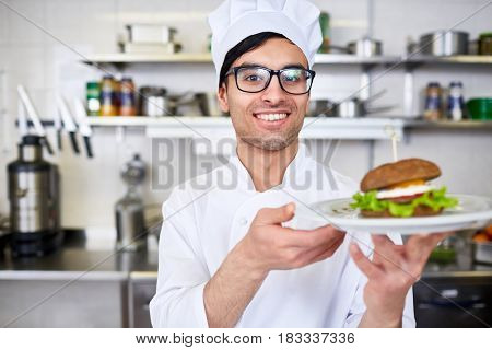 Happy chef serving hamburger on plate