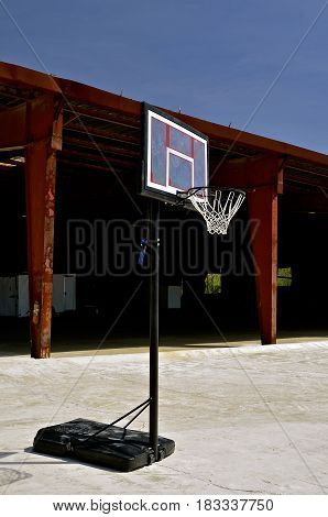 A lone portable basketball stands in front of a closed industrial building and warehouse.