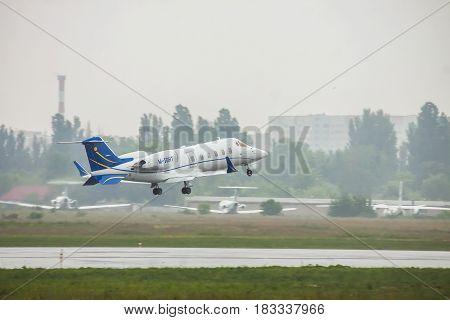 Kiev Ukraine - June 5 2012: Bombardier Learjet 60 business jet is taking off in heavy rain in summer