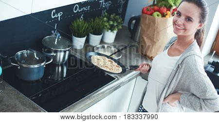 Young woman cooking pancakes at kitchen standing near stove.