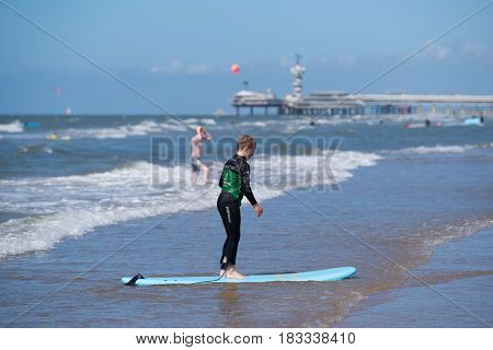 SCHEVENINGEN NETHERLANDS - JULY 3 2016: Unknown boy learning to ride on his surfboard at the dutch north sea coast