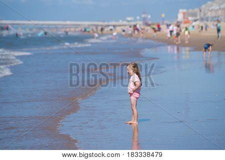 SCHEVENINGEN NETHERLANDS - JULY 3 2016: Unknown little girl enjoying the waves at the North sea beach