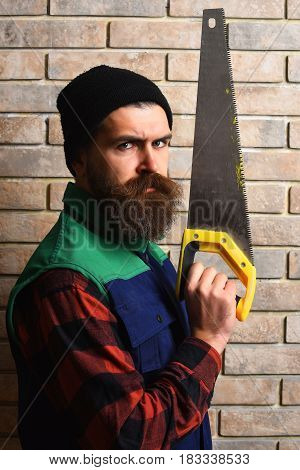 Bearded Builder Man Holding Saw With Serious Face