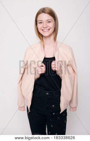 Fashion Young Woman Smiles, Confused Looking At The Camera On A Gray Background