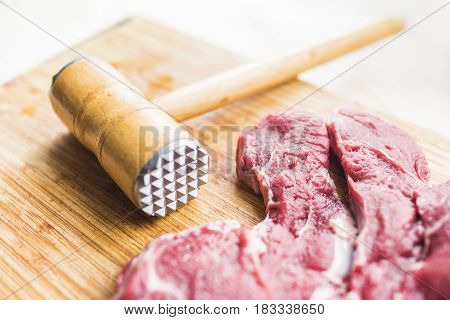 Freshly bright red meat and a light wooden hammer to beat the meat on a bamboo cutting board. Beautiful and healthy cooking concept.