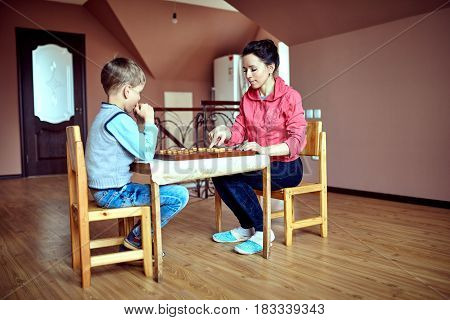 Mom and son playing draughts or checkers board game
