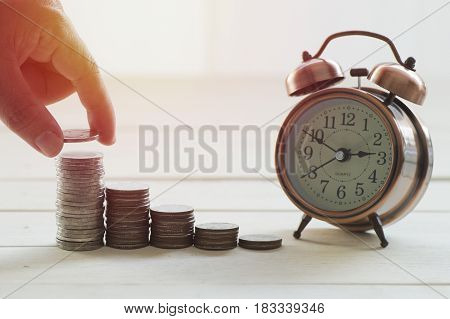 hand put money on pile of coins concept in growth save and investment in business