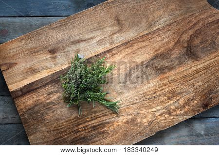 Fresh rosemary and thyme herbs on a cutting board