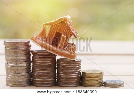 house model on money coins savings plans for housing green background financial concept
