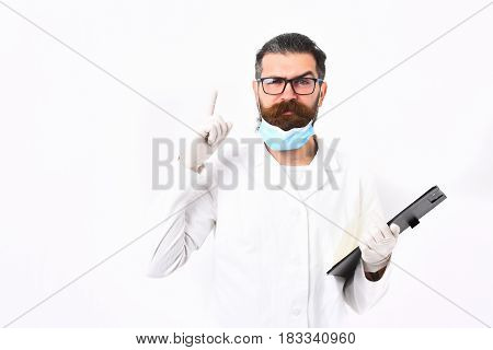 Bearded man long beard. Brutal caucasian doctor or unshaven hipster postgraduate student in mask and medical gown holding clipboard isolated on white studio background. Medicine concept