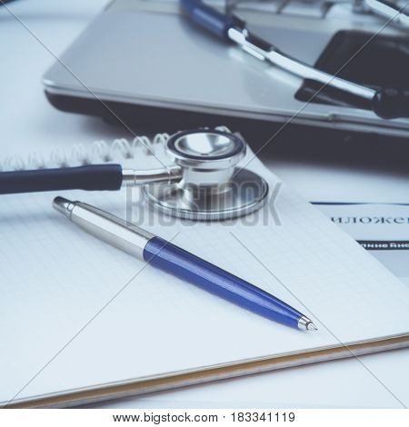 Stethoscope with clipboard and laptop on the desk