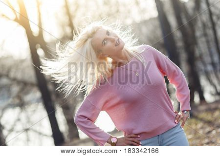 Portrait of long-haired model in jacket at wood