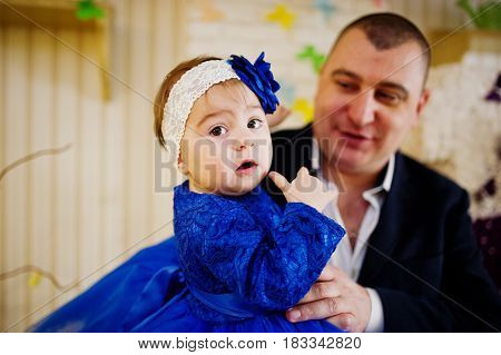Cute little baby girl at blue dress on hands of father.