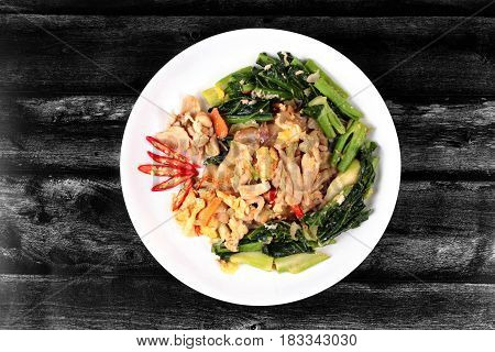 Thai Chinese food Fried big noodle with marinated chicken in soy sauce and vegetable call Sen Yai Pad Cee Oue in Thai.
