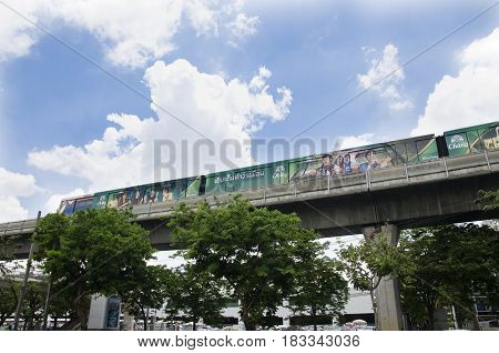 Cityscape And Bts Or Skytrain Running To Stop At Mo Chit Railway Station With People Walking And Tra