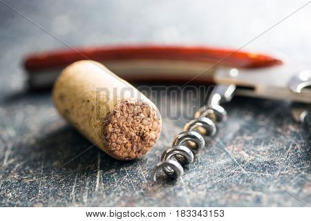 Cork and corkscrew on old table.