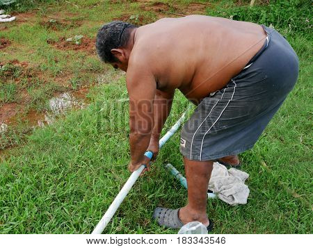 Thai Fat Man Older Work Repairing And Connect Pipe In Garden