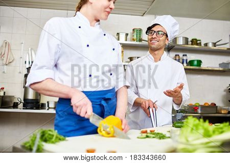 Contemporary chef in uniform consulting his trainee in the kitchen