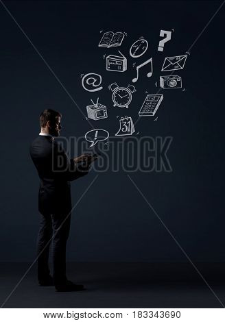 Businessman sending sms with a smartphone. Black background with copyspace. Business, office and internet communication concept.