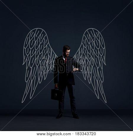 Business angel over dark background. Investment, business, sponsor concept.