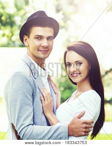 Young beautiful couple of hipsters: hugging in the park. Love, relationship, dating: concept.