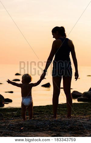 Silhouette of a mother and her baby on the beach in the sunset. Family, love, parenthood, concept.