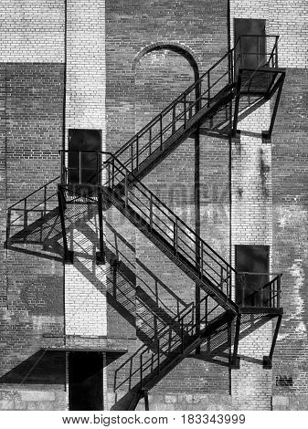 Steel stair and black doors on old industrial building brick wall. On direct hot sun. Black and white photo