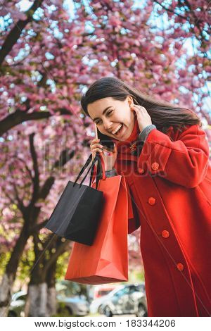 woman stands with paperbags and talking on the phone in the middle of tha street with blooming trees