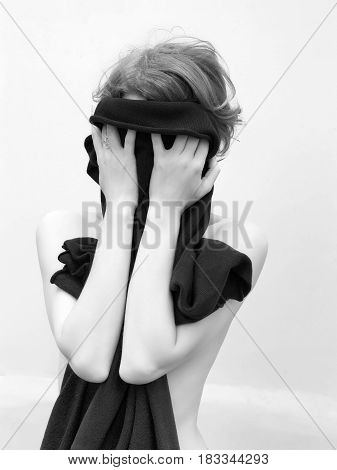 Girl with naked shoulders face and body covered by hands and dress. Black and white photo on white wall background.