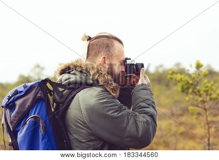 Handsome, bearded guy hiking in swamps and taking pictures of autumn forest. Camp, adventure, trip, concept.