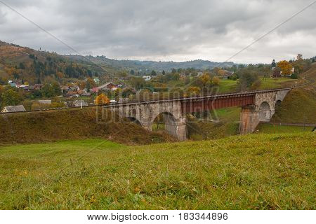 Old railway bridge and mountain village. Carpathians Ukraine