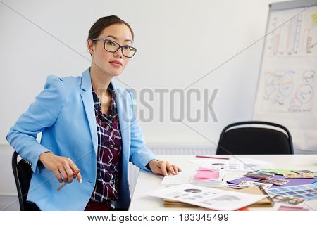 Businesswoman sitting by workplace and writing plan of new project