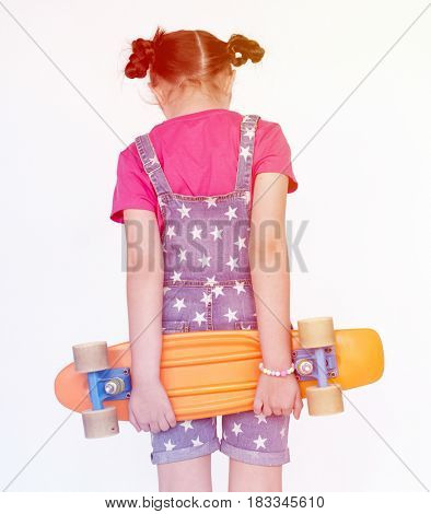 Little Girl Holding Skateboard facing other side