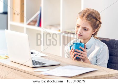 Little Girl Pretending To Be Businesswoman And Working With Laptop In Office