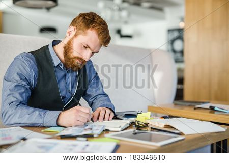 Young man making notes in notebook after analyzing data