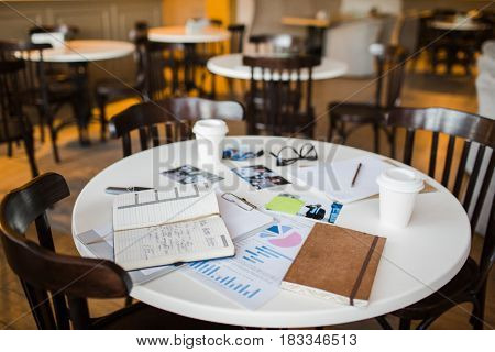 Round table with business objects and three chairs near by