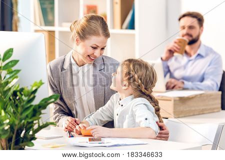Young Mother And Daughter Talking And Hugging In Business Office, Father Behind