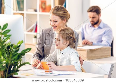 Young Mother And Daughter Hugging And Looking On Monitor In Business Office, Father Behind