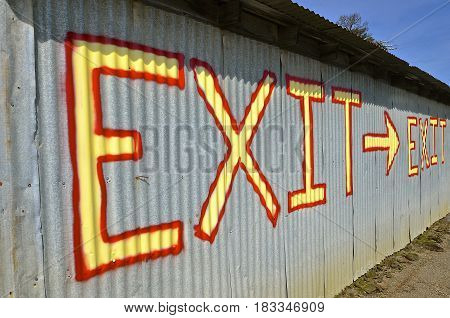 Brightly colored exit sign printed on a steel corrugated building  provides directions with an arrow.