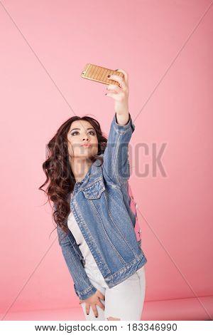 girl in denim jacket makes sjelfi on phone