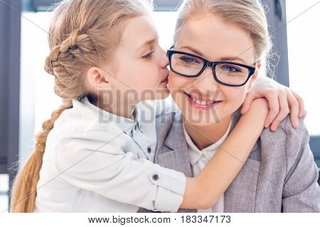 Young Mother And Adorable Daughter Hugging And Kissing In Office