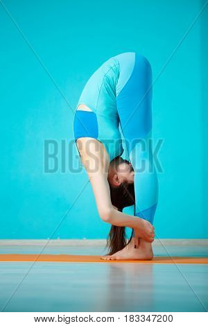 Sportswoman practicing yoga in gym on blue background