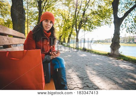 Young stylish woman sits on bench after shopping with paperbags