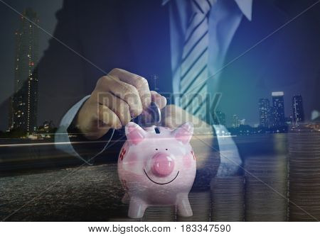 double exposurehand of businessman put money on pink of piggy bank and pile of coins and night city concept in growth save and investment in business