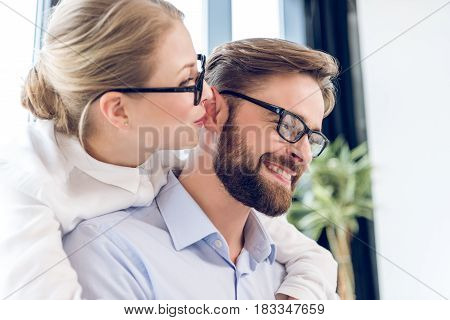 Businesswoman And Businessman With Eyeglasses Hugging And Working With Laptop In Office