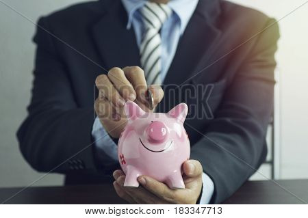 hand of businessman put money on pink of piggy bank concept in growth save and investment in business
