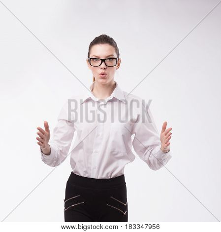 Young happy woman portrait of a confident businesswoman showing presentation, pointing paper placard gray background