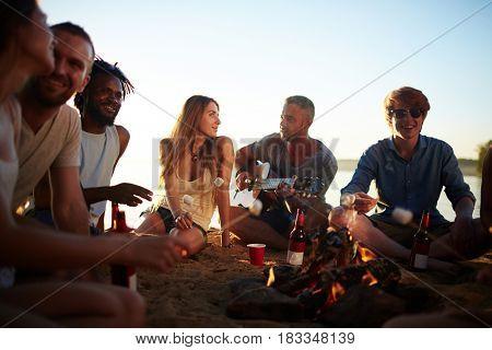 Friendly guys and girls spending summer evening around campfire